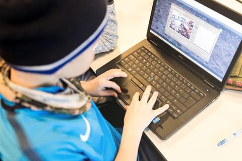 En grundskoleelev skriver på en computer